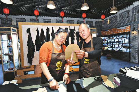 王国中(右)在店内制鞋。
