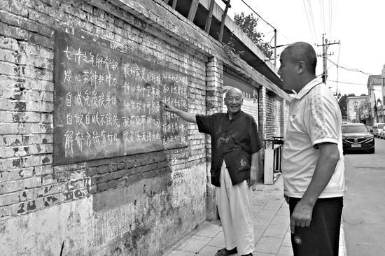 原小平站在黑板报前讲解自己编的养生类打油诗。