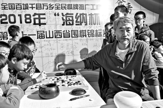 江铸久(右)与小棋手们进行车轮战。图片由主办方提供