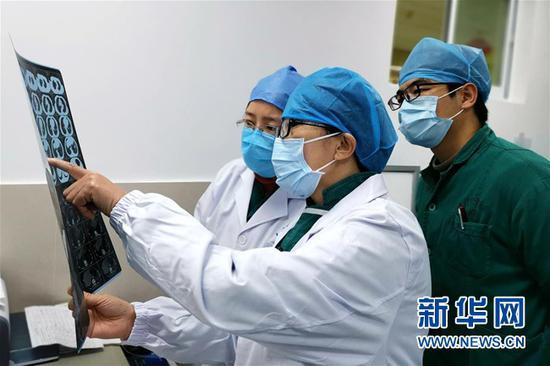 山西省支援湖北省天门市的医护人员在和天门市中医医院的医护人员(右一)查看病人资料(2月9日摄)。新华社发(田弢摄)