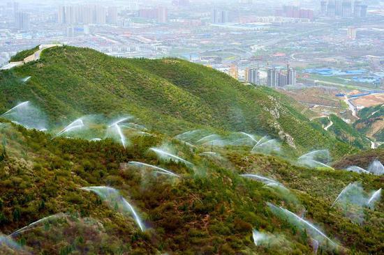 太原市玉泉山的喷灌作业正在进行(2016年4月12日摄)。 新华社记者 曹阳 摄