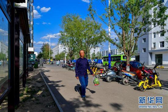 从赵家洼村搬迁而来的曹六仁走在岢岚县广惠园移民新区的街道上(5月20日摄)。 新华社记者 曹阳 摄