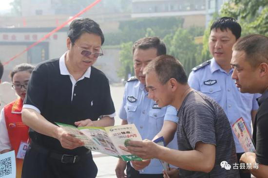 吉县长、崔局长向群众讲解禁毒宣传手册