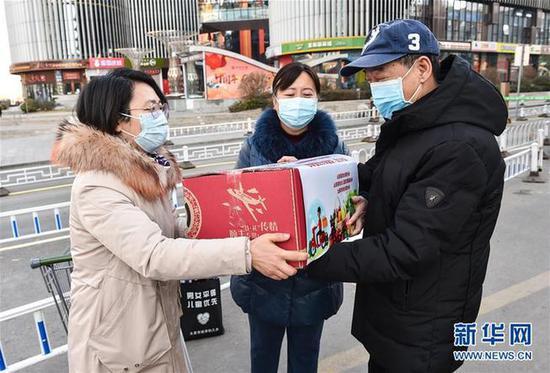 """2月10日,工作人员将""""暖心包""""送给支援武汉医疗队队员王芳的父亲(右)。新华社发(柴婷 摄)"""