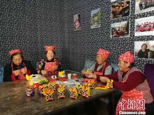 """28日,山西省长治市上党区西岭村,61岁的马春花和几位村民正在制作""""贴布绣""""手工艺品。 卫玮 摄"""