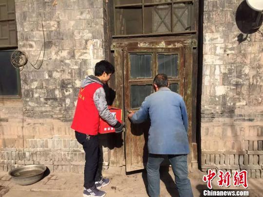 志愿者帮老人将物品搬回家。 李泊萱 摄