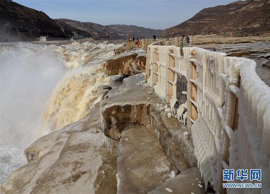 12月7日,游客在黄河壶口瀑布拍摄冰挂景观。