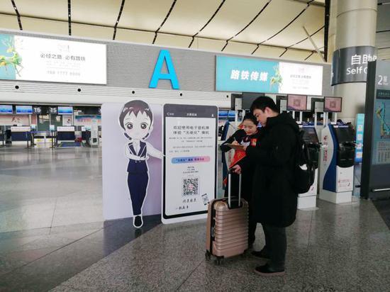 """图为机场工作人员为乘客讲解""""无纸化""""乘机"""