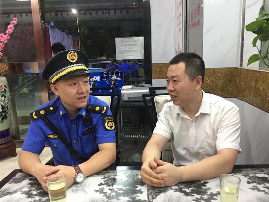 唐槐执法中队市容队长李园田与某烧烤店老板交谈