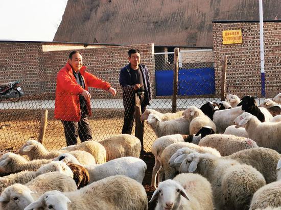 石刚(左)在三祝村扶贫一线工作