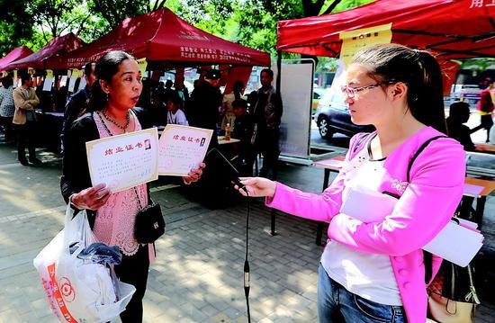 """经过""""吕梁山护工""""专业技能培训的李女士前来参加护工专场招聘会,她开心地给记者展示她和同伴的结业证书。赵泉 摄"""
