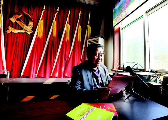 程厚福通过大喇叭为村民讲解党和国家的方针政策。