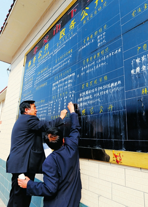 程厚福(左一)在村务公开栏上填写相关内容。