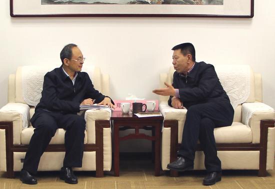 山西证监局局长孙才仁(右)与忻州市市长郑连生进行交流