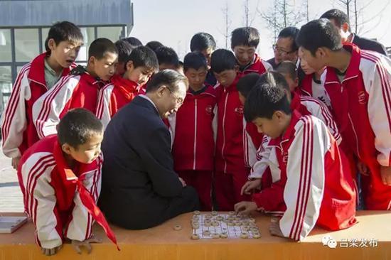 2017年4月25日,温家宝在兴县一二0师学校作地理讲座之余,与学生们一起下象棋。