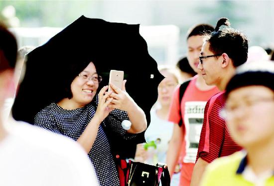图为考场外,领队老师给梳小辫子的考生拍照留念。 牛晨阳 摄