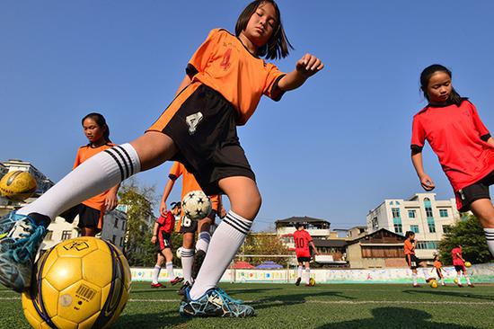 2016年12月8日,在贵州省榕江县古州镇第二小学,校园足球队在进行足球训练。