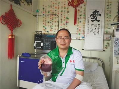 捐献完毕后,王炳效手拿从他血液中分离出的造血干细胞混悬液。受访者供图