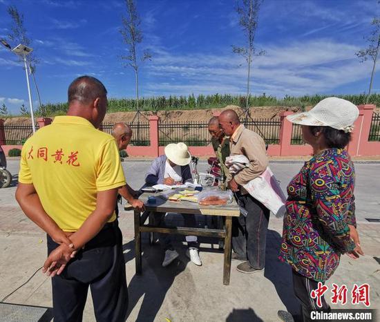 村民杨的师正在忙着收购当地村民摘的黄花。 杨杰英 摄