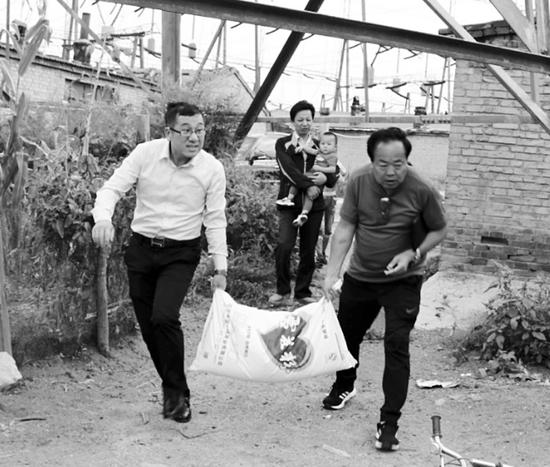 山西晚报记者(右一)帮夏先生(左一)给小月圆家送面粉。