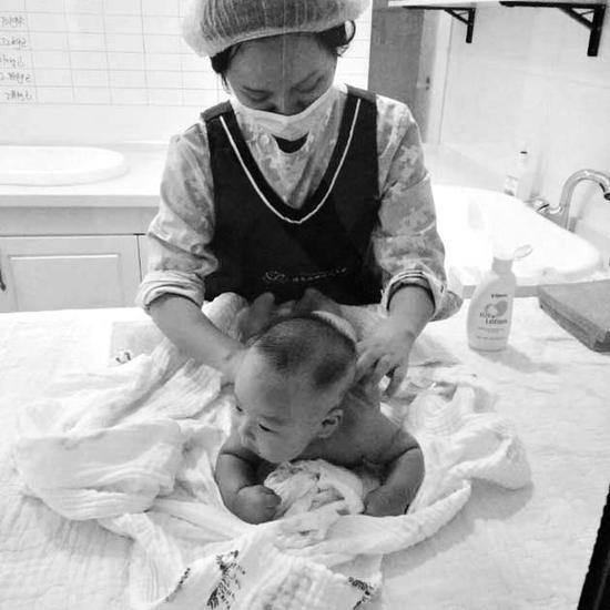 育婴师正在给孩子做抚触