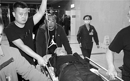 西山护卫支队的工作人员将受伤的宣树宏送往医院。