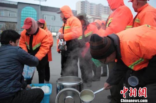 26日早上7点多,山西省长治市长子县市场监督管理局附近,已经在寒风中工作了两三个小时的环卫工人们排着队领取热腾腾的早饭。长子县新闻中心 供图