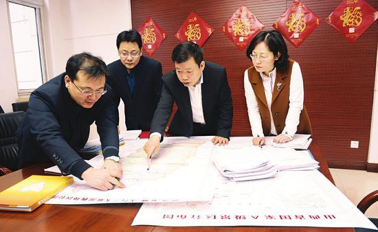 王文保(右二)正与相关人员研究黄河、太行、长城三大旅游板块的开发事宜。(资料图)