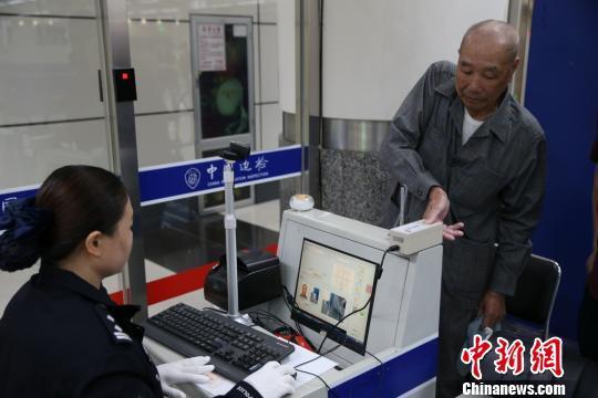 深圳湾边检民警在临时自助通关信息采集点为旅客采集信息 黄钊 摄