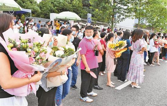昨日下午,在宝安中学校门口,许多考生家长手捧鲜花等候着。 深圳商报记者 陈锡明 摄