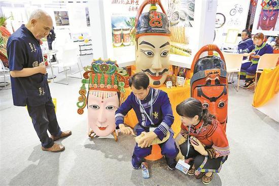 ▲毛南族民间傩面雕刻艺人方文展现场雕刻傩面。