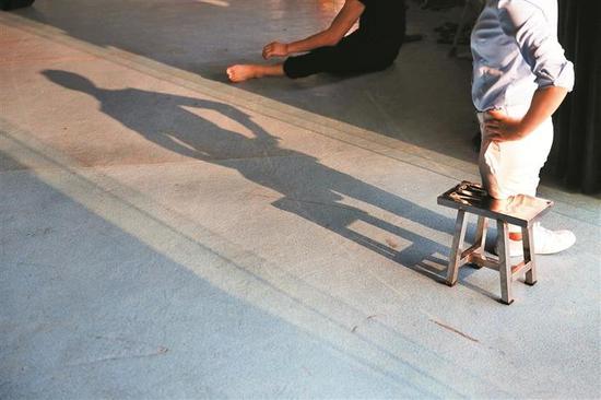 1 夕阳照进排练室,舞者陈伦会的影子被拉得长长的。