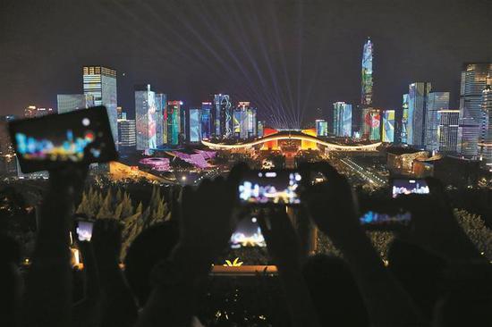 莲花山顶,市民观看灯光秀表演,并用手机记录炫彩瞬间。