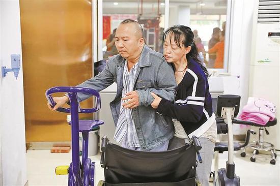 ▲吴琼帮助比自己重70多斤的杨猛做康复训练。