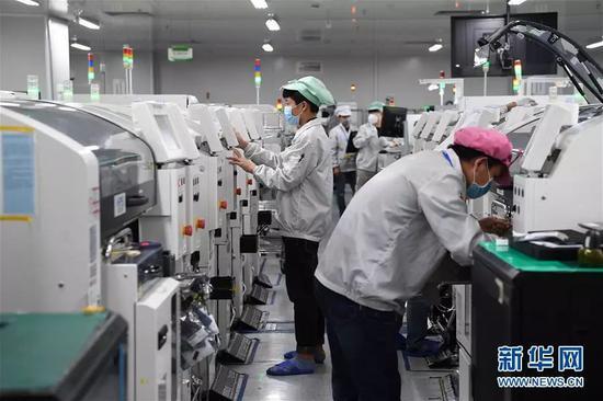 2月10日,在深圳龙岗区一家工业园区的生产车间,复工的工人佩戴口罩工作。