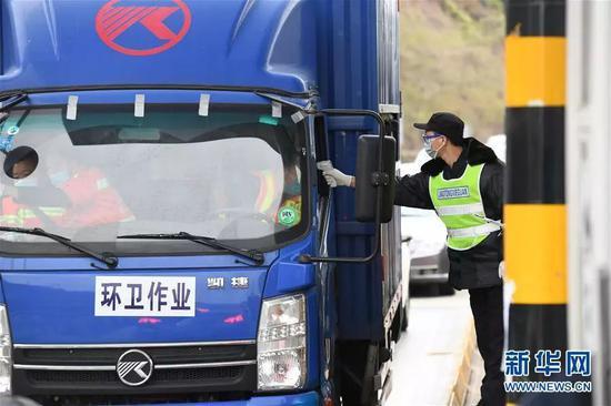 在深圳和东莞市际交界处的龙大高速罗田收费站交通联合检疫站,执勤人员对进入深圳的车辆进行检疫排查(2月9日摄)。