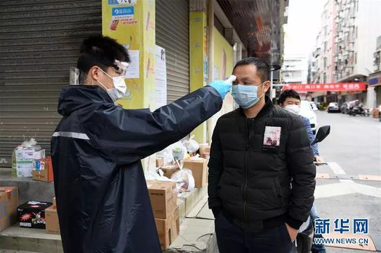 在深圳市宝安区新安街道海乐社区的城中村,工作人员为居民测量体温(2月9日摄)。