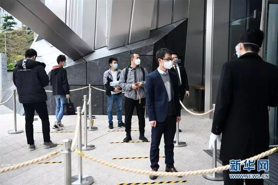 2月10日,位于深圳福田区CBD的平安金融中心开始复工,企业员工间隔排队有序进入写字楼。