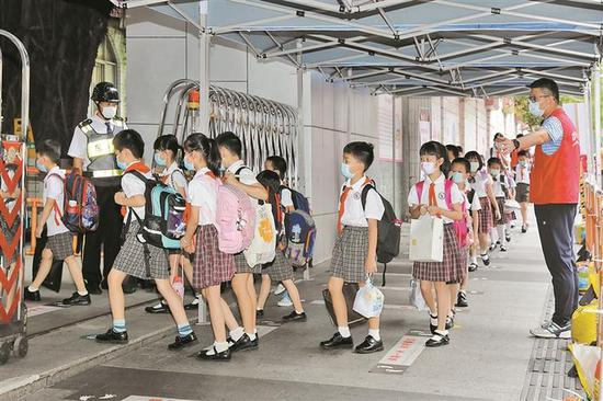 ▲学生在义工引导下有序排队进入校园。深圳晚报记者 张焱焱 摄