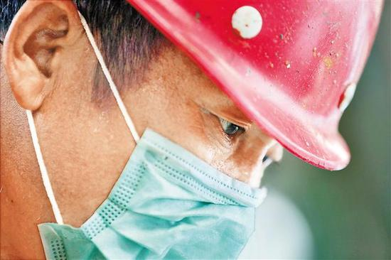 戴着口罩神情专注的建设者。