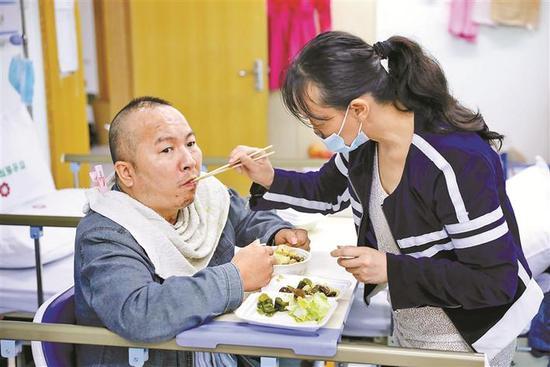 ▲吴琼悉心照料杨猛吃饭。