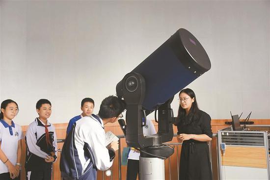 孩子们用天文望远镜认识天体。
