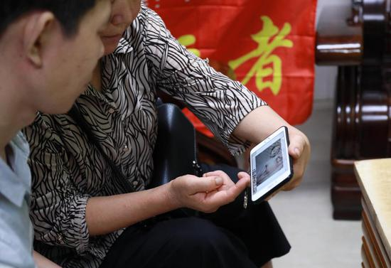 ▲廖兴菊 ( 右 ) 拿出手机给王强看儿时的照片。