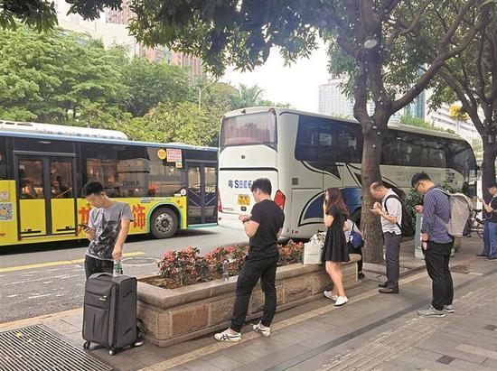 ◀深南东路南侧大剧院地铁站E出口处公交车道上,网约大巴在此揽客,导致其后的公交车无法通过公交车道进站,只好绕道进站。
