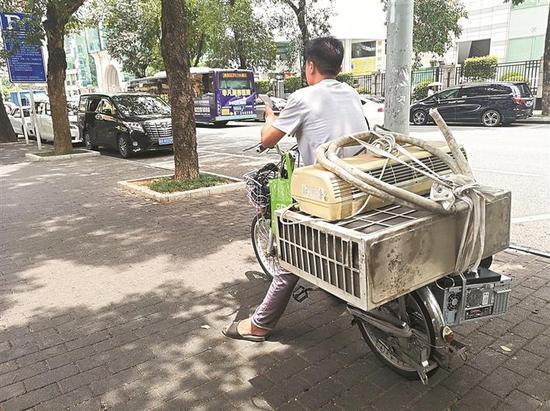 一名散工正载着旧空调,称可以提供上门安装服务。 本版图片均由深圳晚报记者 李瑶娜 实习生 林咪玲 摄