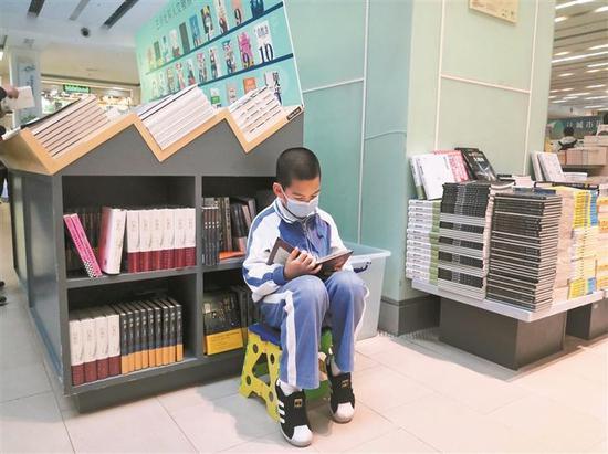 ▲戴着口罩在中心书城阅读的小读者。