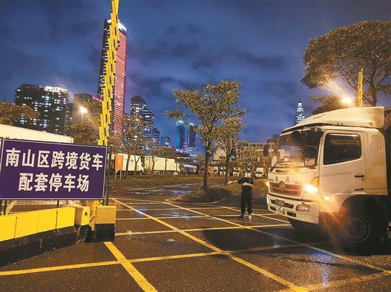 夜间工作人员指挥车辆进入停车场。