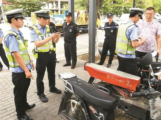 执法人员查扣违法上路摩托车。