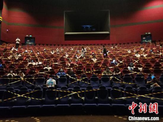 7月23日晚,万达影城石景山万达广场店,观众戴口罩分隔而座,等待零点场开始。中新网任思雨 摄