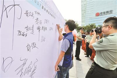 应征青年在签名墙上签名。